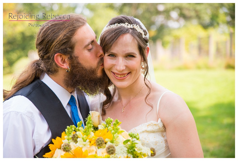 Bearded groom kissing lovely bride