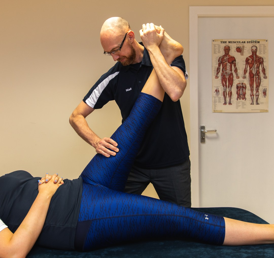 Therapist doing physiotherapy on client