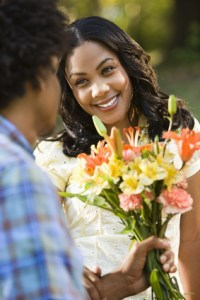 Man giving smiling woman bouquet of flowers.