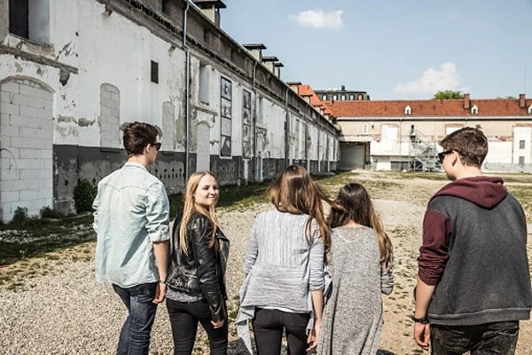 Teenagers strolling past abandoned buildings and seemingly on their own.