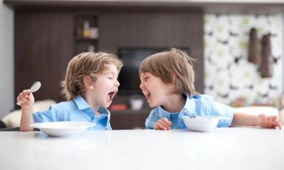 Two kids in school uniform eating breakfast