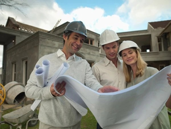 Architect and couple looking at blueprints outside house under construction