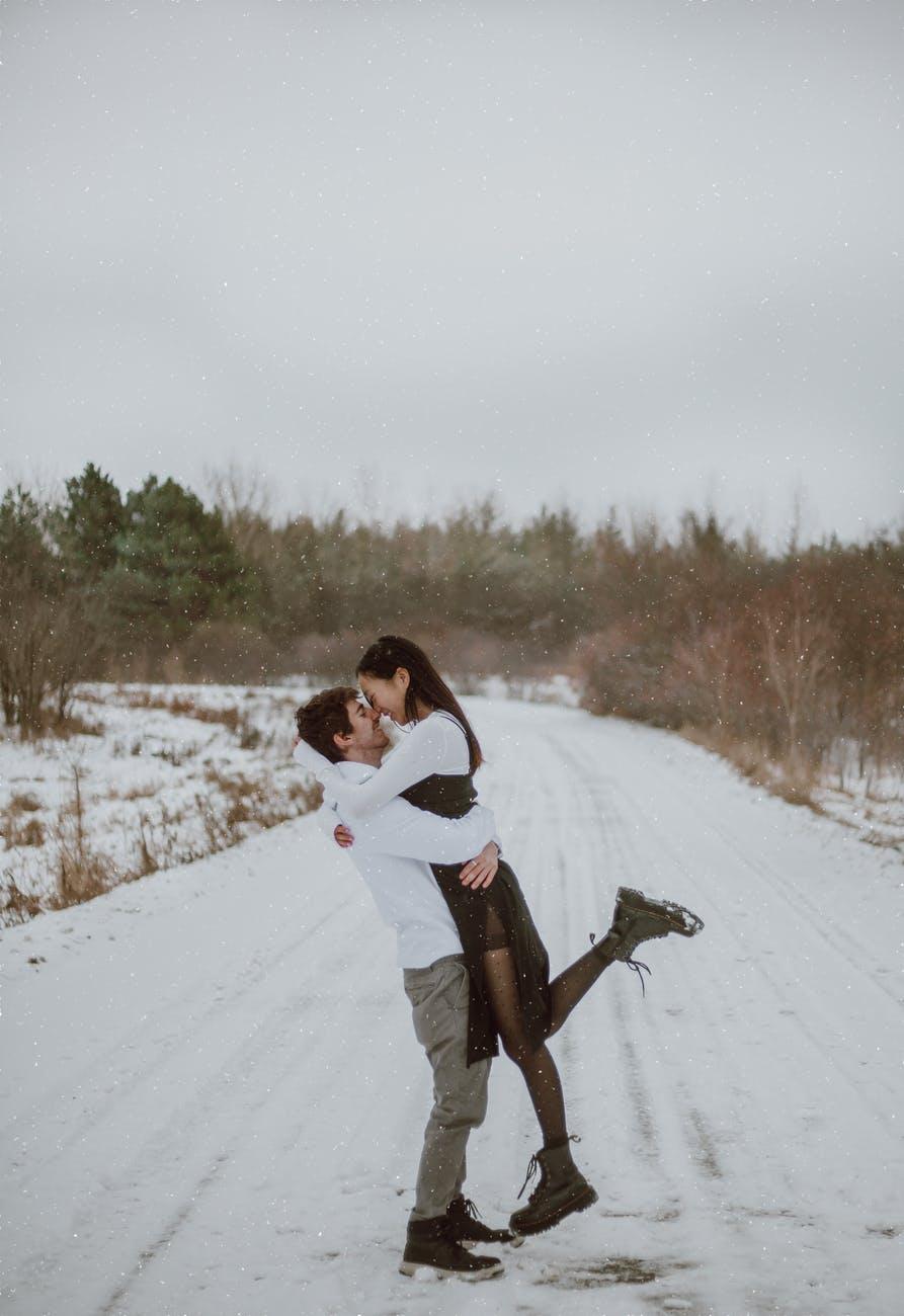 happy multiethnic couple embracing on snowy road