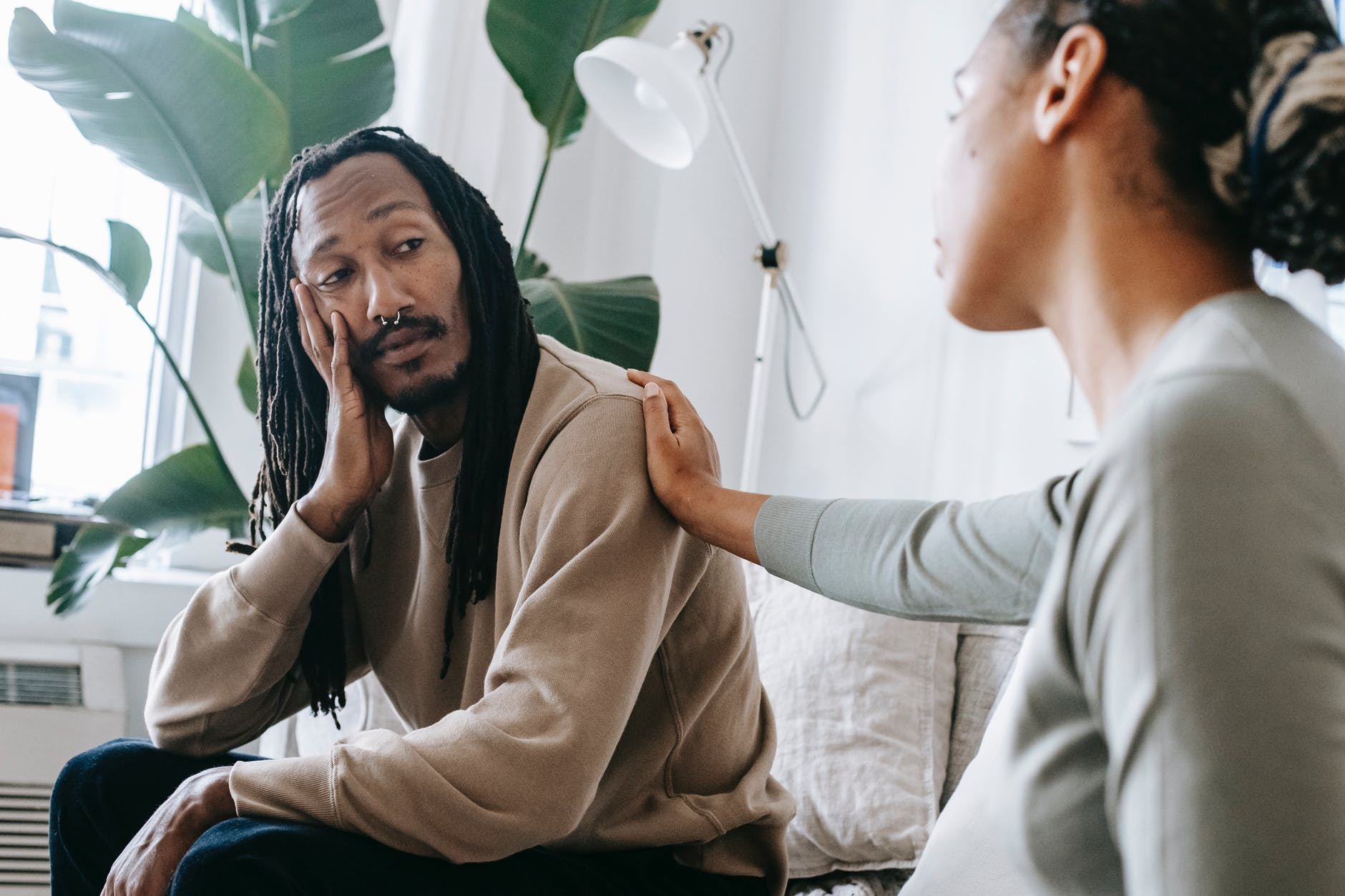 ethnic psychologist touching black depressed clients shoulder