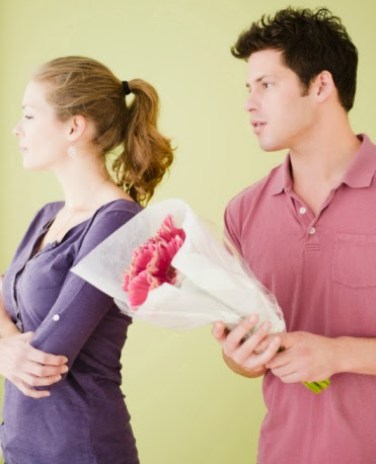 Man offering unhappy girlfriend flowers