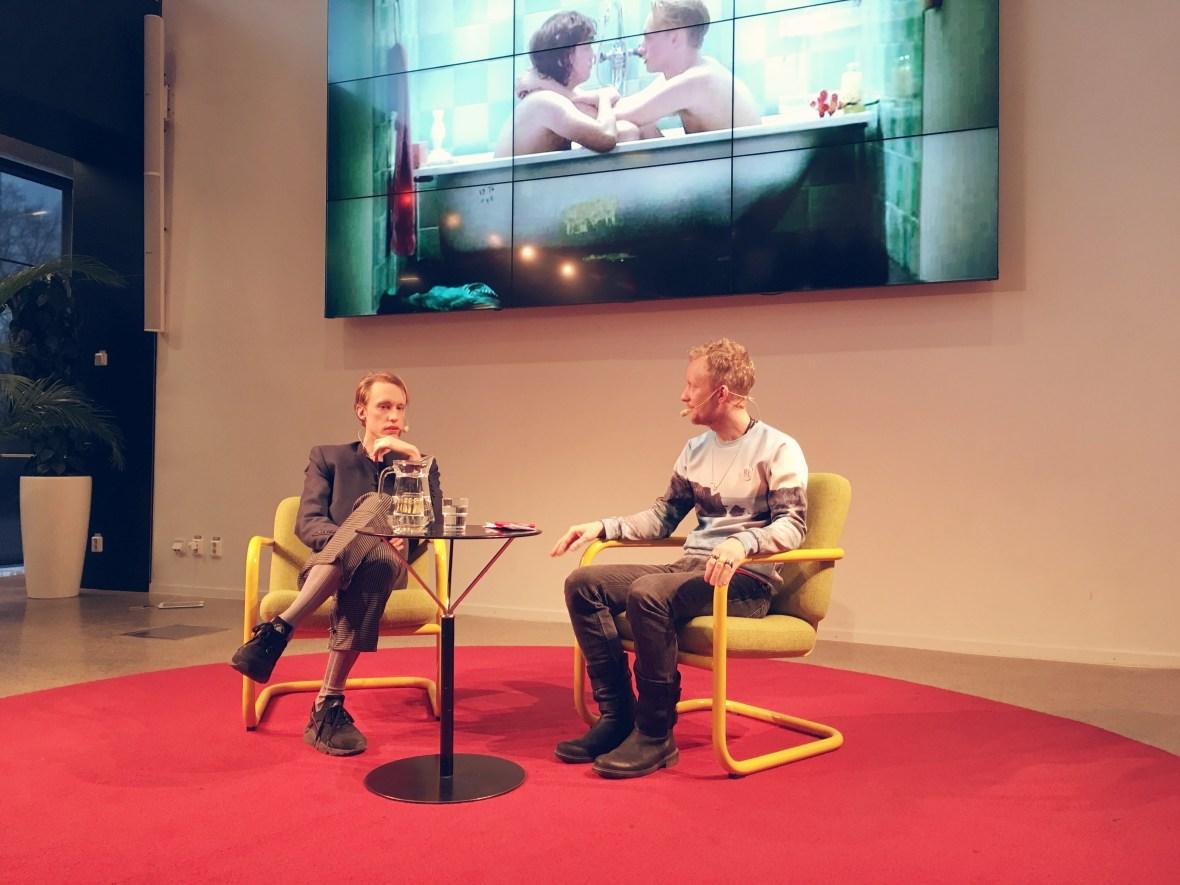 Ester Martin Bergsmark och Simon Ceder framför stor skärm med filmkaraktärer i badkar