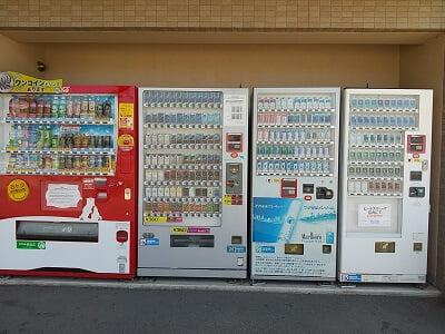 岡田商店の敷地内にドリンクとたばこの自動販売機の写真