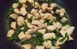 鶏肉をフライパンで炒めピーマンも入れて調味料で味付けする写真