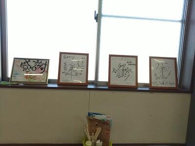 かき小屋 匠ちゃんの窓際に有名人のサインがたくさんある写真