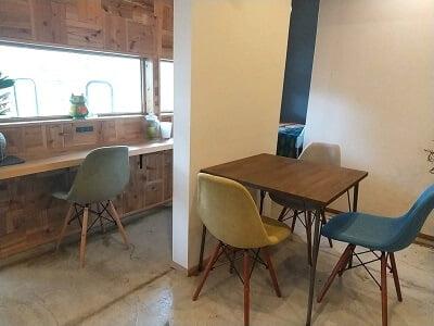 Salute食堂の1階左のカウンター席と柱横の小さいテーブル席の写真