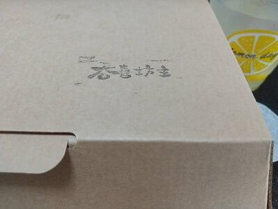 呑喜坊主のテイクアウト紙箱に店名がある写真