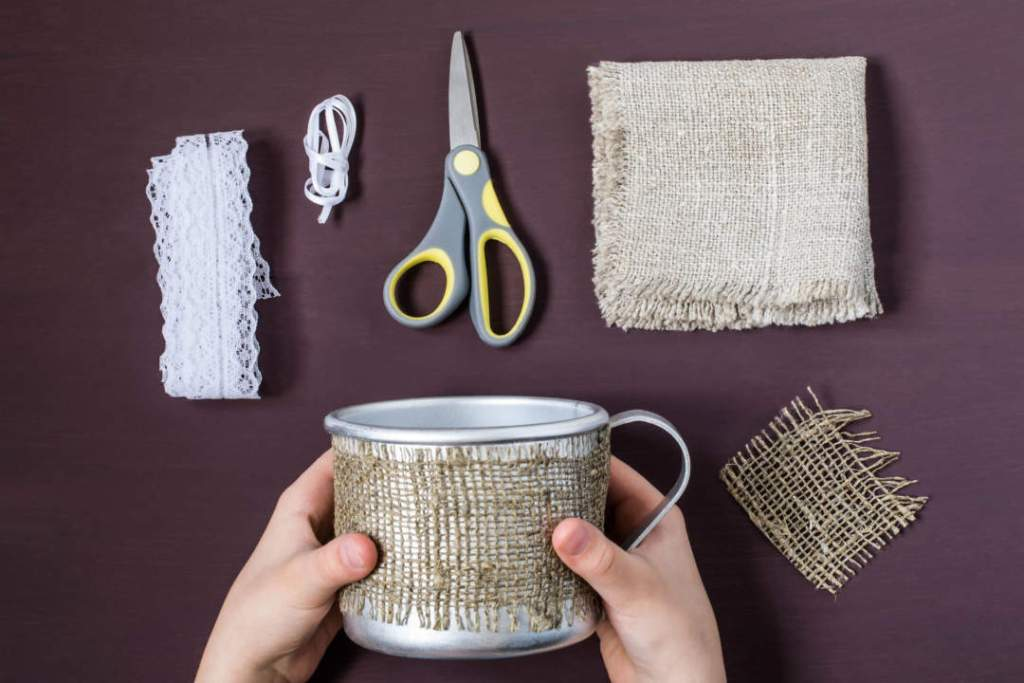 Step 2. Attach the strip of burlap to the mug. <br>  When I was in elementary school, we used coconut coir instead of this. You can also use strips of colorful cloth.