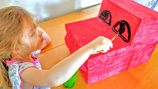Izzy pictured, painting her dragons eyes on with black paint very carefully.