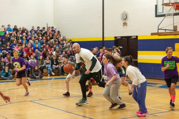 Anthony playing basketball with students and staff at Armstrong Middle School