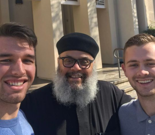 Priest with beard, flanked by students in exterior photo
