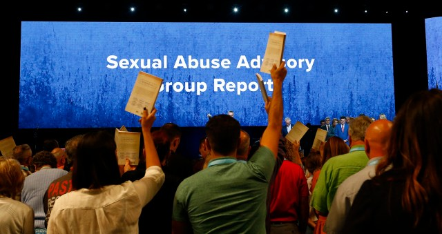 Messengers hold up an SBC abuse handbook while taking a challenge to stop sexual abuse during the annual meeting of the Southern Baptist Convention at the Birmingham-Jefferson Convention Complex, June 12, 2019, in Birmingham, Alabama. RNS photo by Butch Dill