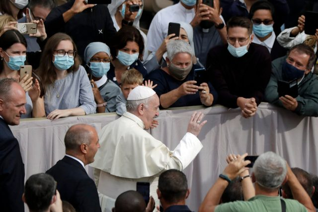 People wear face masks to prevent the spread of COVID-19 while Pope Francis waves as he arrives for his first general audience with faithful since February, when the coronavirus pandemic broke out, in the San Damaso courtyard at the Vatican, on Sept. 2, 2020. (AP Photo/Andrew Medichini)