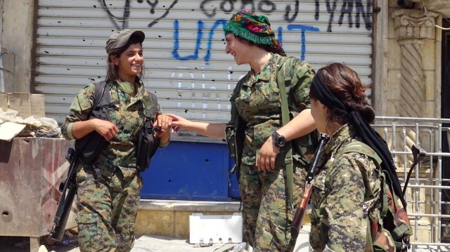 "A group of fighters, part of an all-female Kurdish militia, share a laugh. Photo courtesy of ""The Daughters of Kobani"""