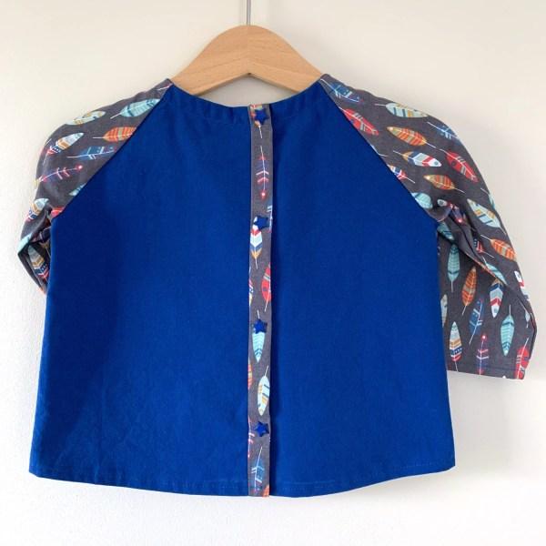Dos d'une blouse garçon sur un cintre