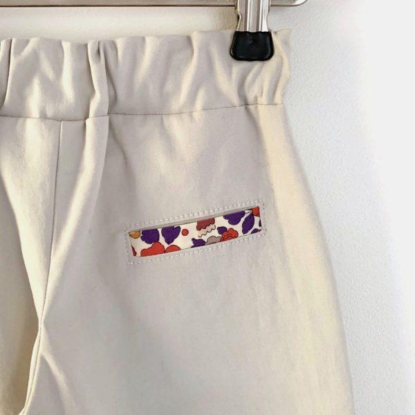 Fausse poche passepoilée d'un pantalon