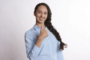 A woman in a blue shirt showing a thumbs up gesture.