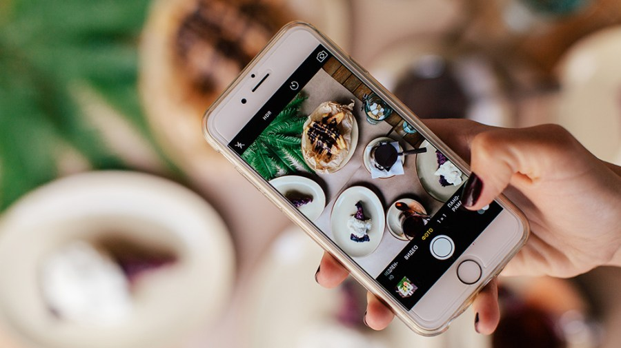 Person taking photos of the food they sell in a restaurant for online sales and ecommerce via their Shopify site.