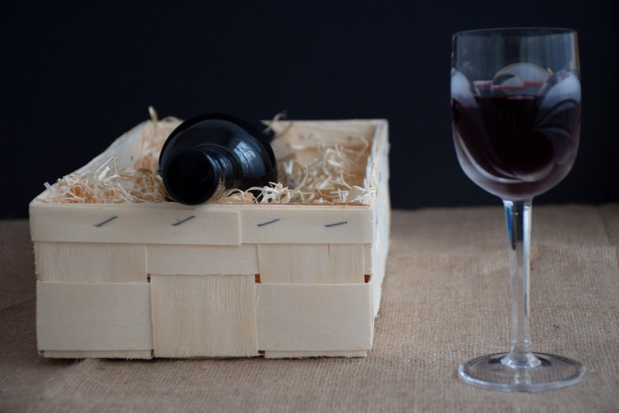 nominated-already-bottle-of-wine-in-wooden-box-with-straw-crystal-wine-glass-with-red-wine_t20_P1ZBAR