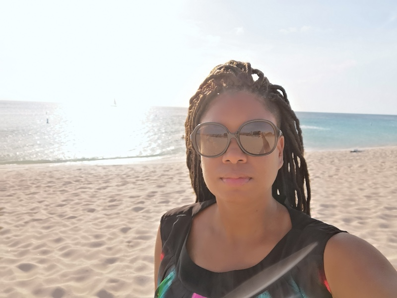 Woman in sunglasses looking at the viewer from a beach in Aruba