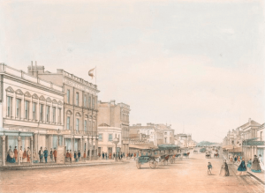 View of a street scene from near Little Bourke Street, looking south towards Queen's Domain and shows Tebbut's Tea, Coffee and Chop House, Dancker's Globe Tavern, Star Hotel, Paterson's City Portrait and a horse and buggy cab rank in the middle of the street.