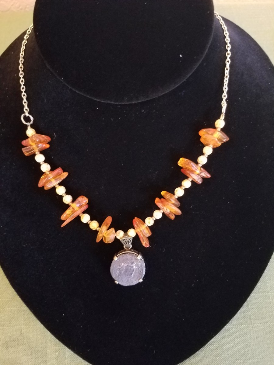 Roman coin flanked with amber necklace