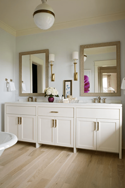 This bright & airy modern bathroom is warmed with antique brass accents.