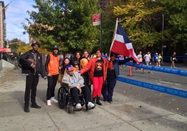 Luz Estrella, junto a su familia, carga la bandera dominicana cerca de la milla 21 en Harlem donde esperó a su hijo, Nelson Flores, que corrió la maratón para recaudar fondos para la lucha contra la leucemia. Foto: Gustavo Martínez/EDLP