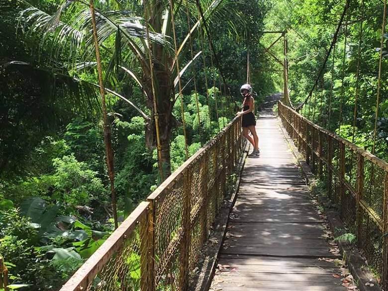 A girl wearing a helmet on a yellow bridge in Sideman, Bali