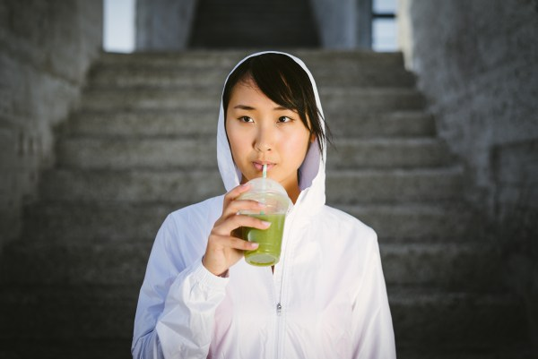 Asian female fitness athlete drinking green vegetable detox smoothie. Sport diet and nutrition concept. Healthy woman portrait.