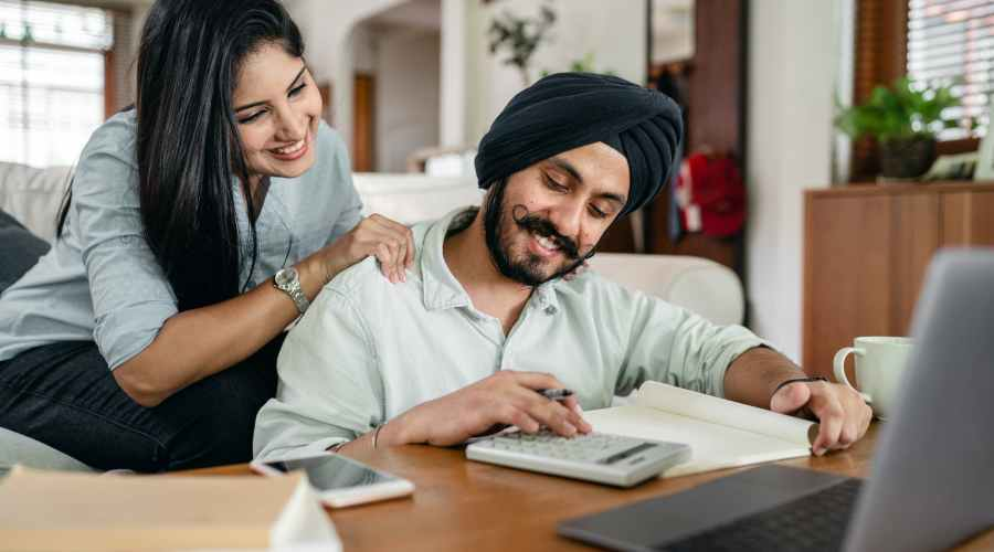 smiling ethnic accountant using calculator while ethnic wife watching behind