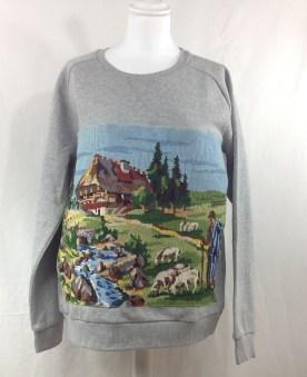 Sweat gris molletonné , taille L , emmanchures basses , customisé avec un canevas motif berger et moutons .