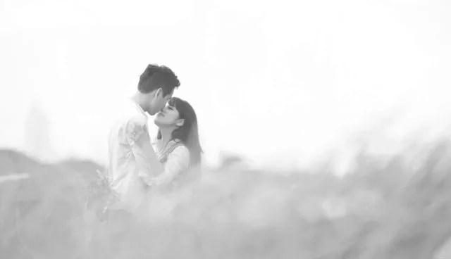 キスをするカップル 草原 自然 見つめ合う ハグ