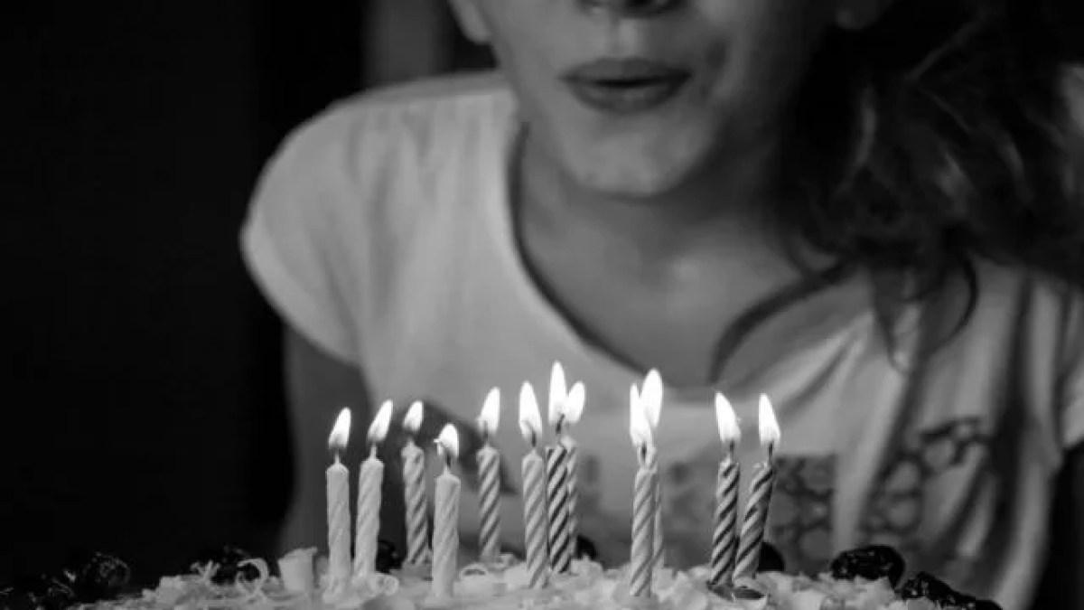 ろうそくを吹き消す女性 誕生日ケーキ