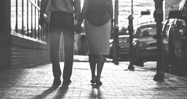 手をつないで通りを歩くカップルの後ろ姿