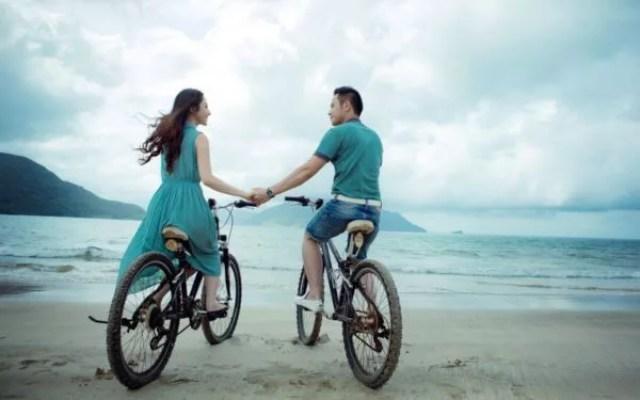 カップル 自転車 手をつなぐ 海 見つめ合う