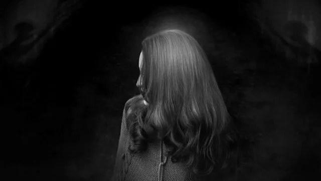 暗い部屋に佇む女性