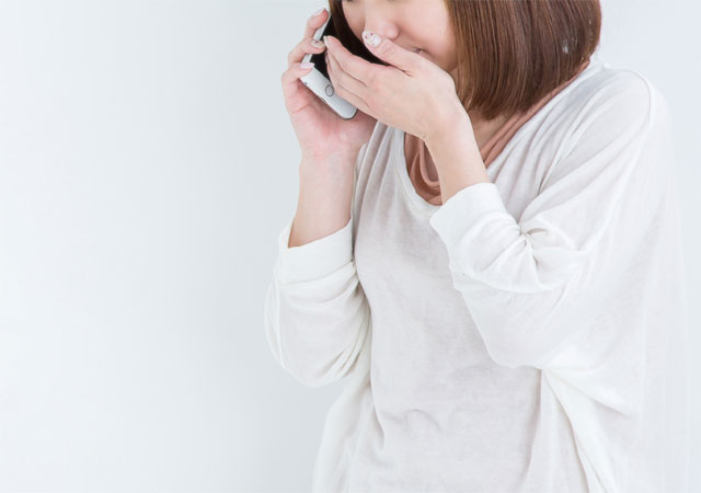 こっそり電話で悩み相談をする女性のイメージ