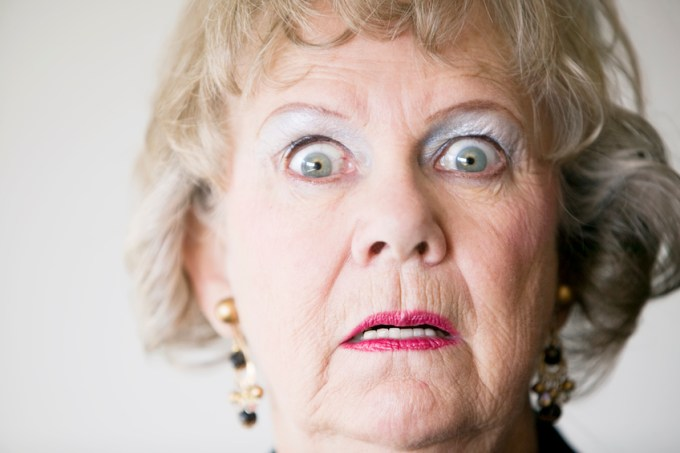Close-up of a senior woman with a horrified look on her face.