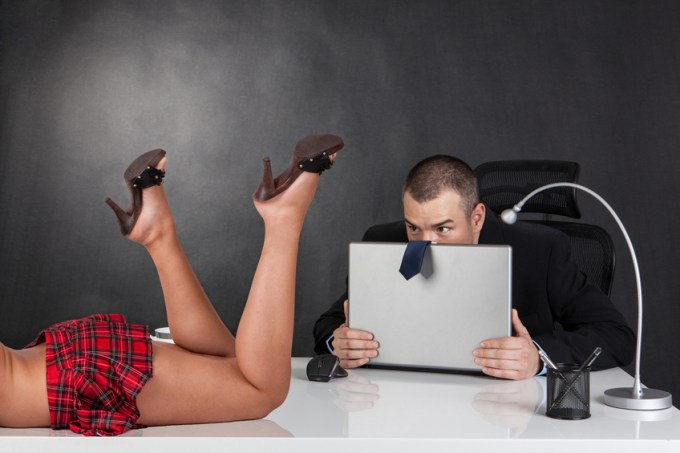 Sexual harassment. Sexy woman is seducing her boss at office