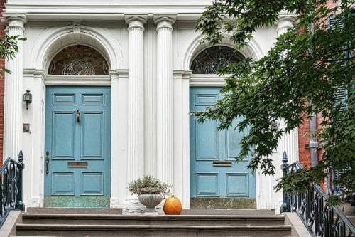 Side by side blue doors against a decorative white arched entry and a single, un-carved pumpkin on the stoop.