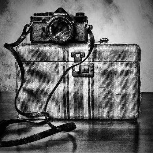 An old Olympus film camera sits atop a small antique make up case. Finished in black and white for vintage effect.