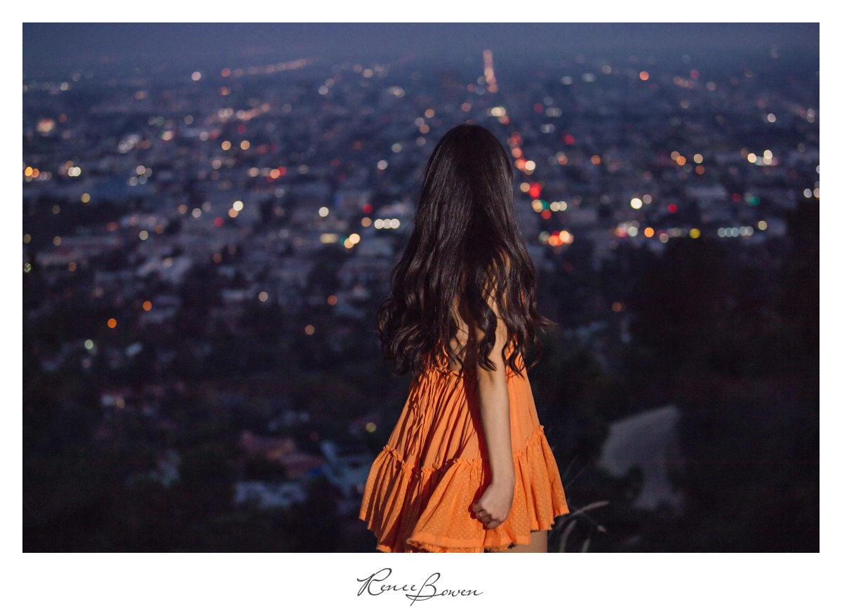 girl in orange dress overlooking hollywood lights