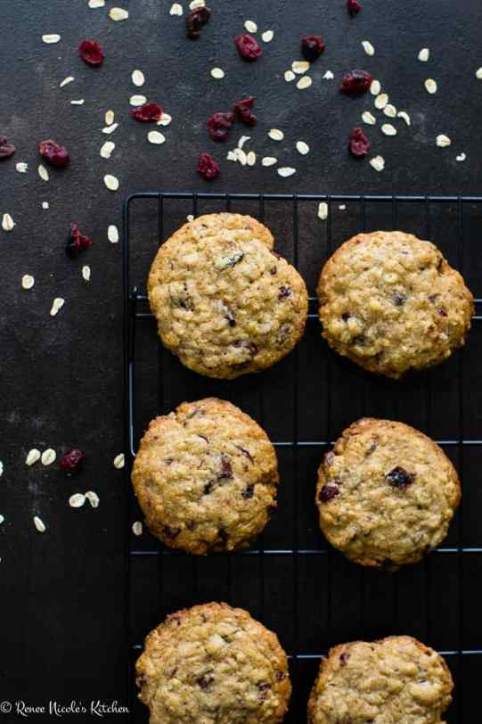 Cranberry chocolate chunk oatmeal cookies on a cooling rack on a dark surface.