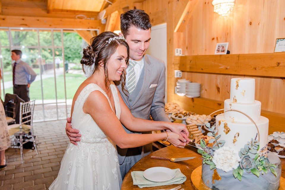 bride and groom cut Bredenbeck's Bakery cake by wedding photographer Renee Nicolo Photography
