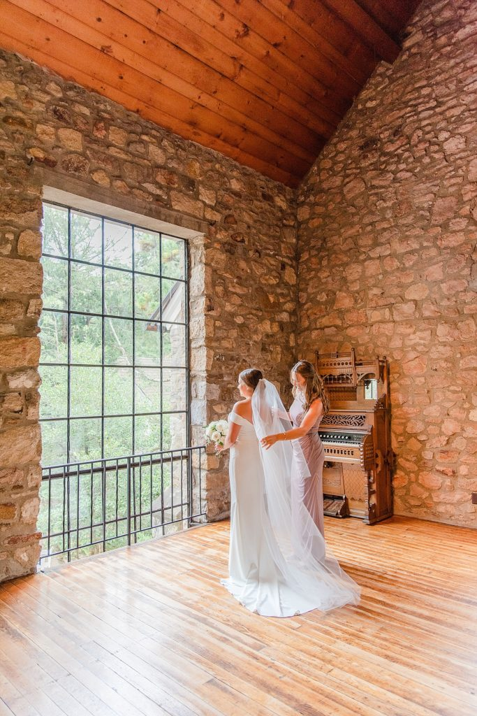 bridesmaid helps bride with veil on PA wedding day with Renee Nicolo Photography